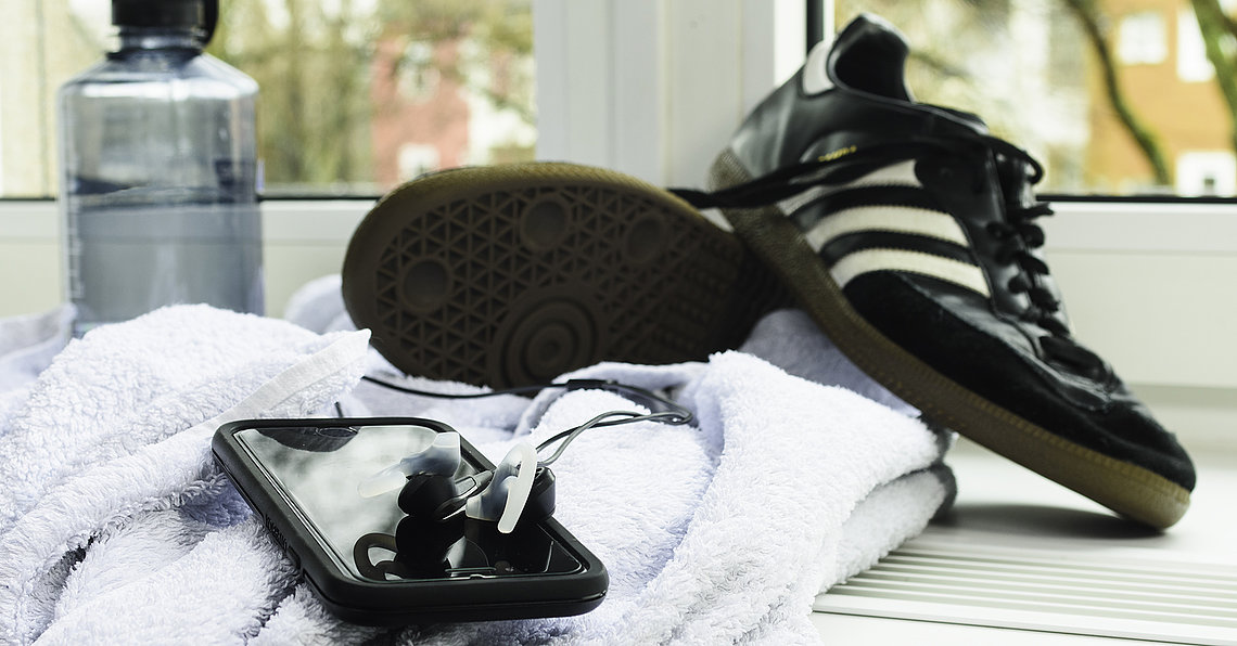 Running shoes, Towel & Smart phone (symbolic)