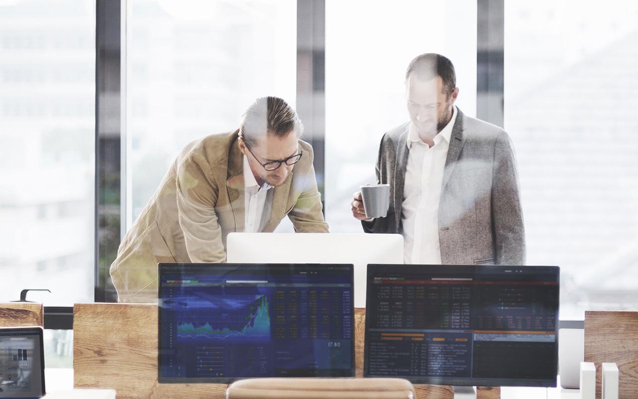 Bild: Ein Mitarbeiter der G DATA Advanced Analytics und ein Partner schauen zusammen auf einen Bildschirm und unterhalten sich
